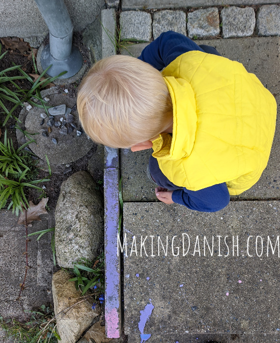 toddler painting with chalk paint outside